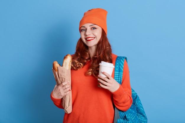 생강 젊은 웃는 학생 서 테이크 아웃 커피와 바게트