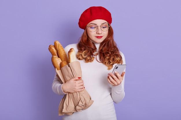 Рыжая молодая женщина в стильной одежде изолирована на сиреневом пространстве
