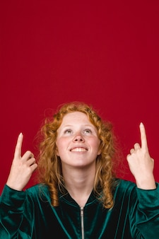 Ginger young woman looking and pointing up