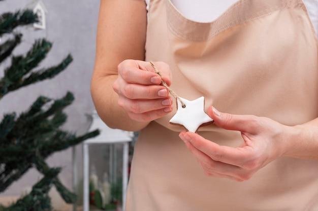 女性の手に釉薬をかけたジンジャーブレッドのアスタリスク。クリスマスツリーの装飾。