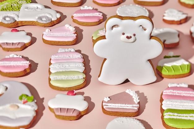 ピンクの背景にさまざまなクッキーの中でジンジャーブレッドクマ