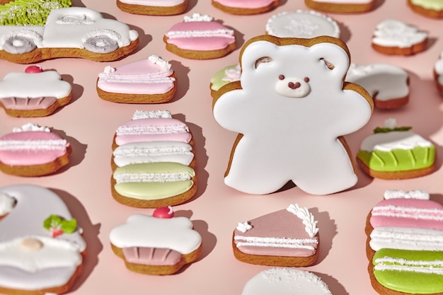 Gingerbread bear among various cookies on pink background