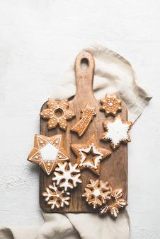 ジンジャーブレッドのクリスマスと新年あけましておめでとうございますクッキー白い背景、コピースペース、垂直の木製カットボード