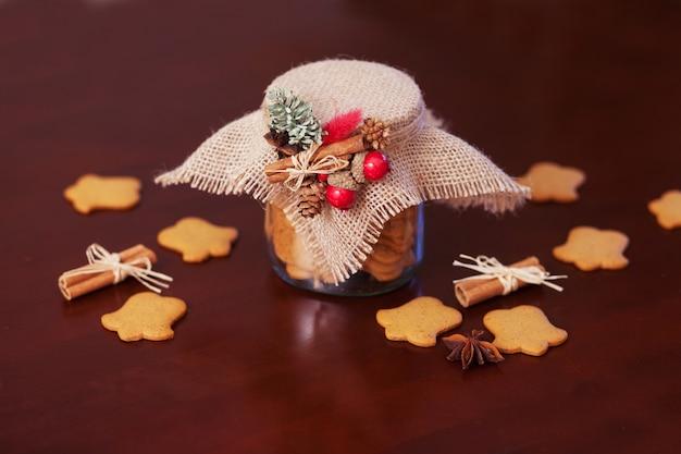 ガラスの瓶にジンジャーブレッドのクリスマスクッキー。クリスマスのスパイスと装飾がクローズアップ。暗い背景。年賀状とクリスマスカード。