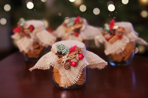 ガラスの瓶にジンジャーブレッドのクリスマスクッキー。クリスマスのスパイスと装飾がクローズアップ。ボケ味と光でお祭りの背景。年賀状とクリスマスカード。魔法のおとぎ話