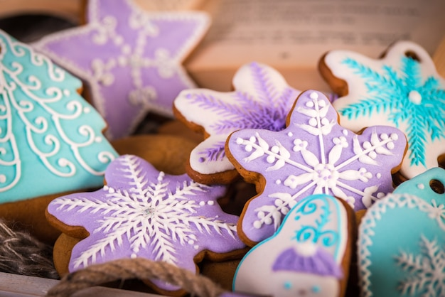 Gingerbread christmas cookies, snowflakes an gingerman. knitted scarf and cinnamon sticks.