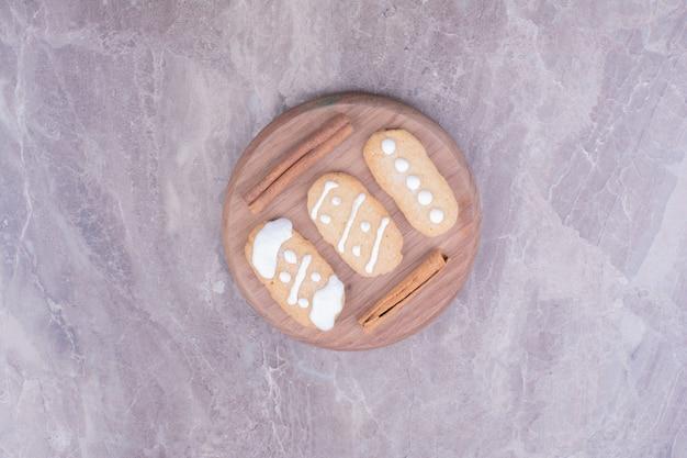 丸い木の板にシナモンスティックが付いたジンジャーブレッドのクリスマスクッキー。