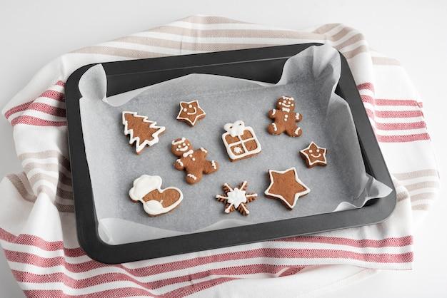 ベーキングシートに艶をかけられた砂糖のアイシングが付いているジンジャーブレッドのクリスマスクッキー。伝統的なベーキング。