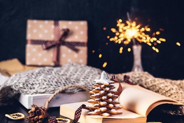 ジンジャーブレッドのクリスマスツリークッキー、1月のページに碑文が書かれた本を開きました。線香花火とギフトが箱に入っています。