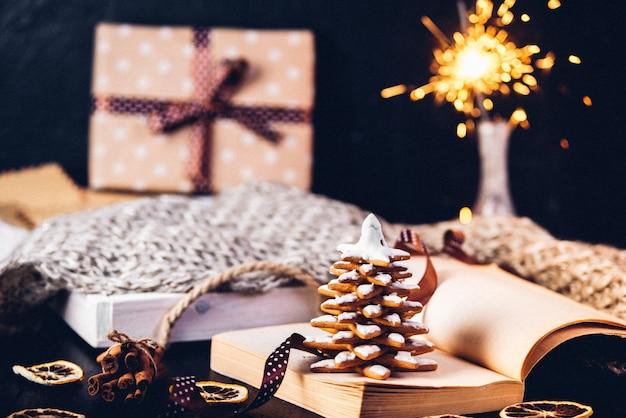 Пряники новогоднее печенье, открытая книга с надписью на странице январь. бенгальские огни и подарок в коробке.