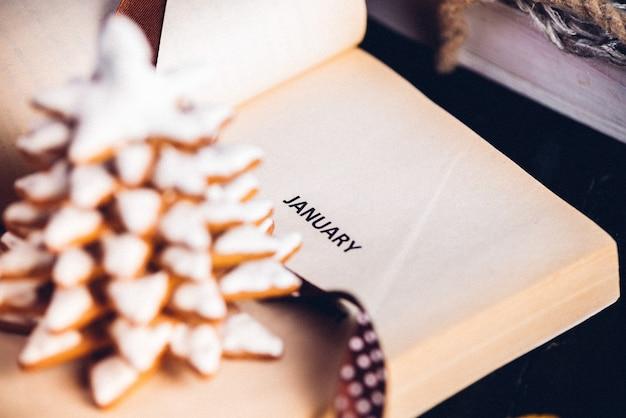 ジンジャーブレッドのクリスマスツリークッキー、1月のページに碑文のある本を開きました。