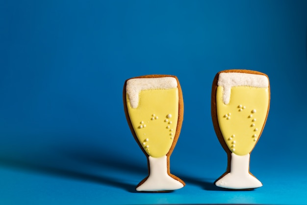 Gingerbread cookie of champagne glass on blue copyspace