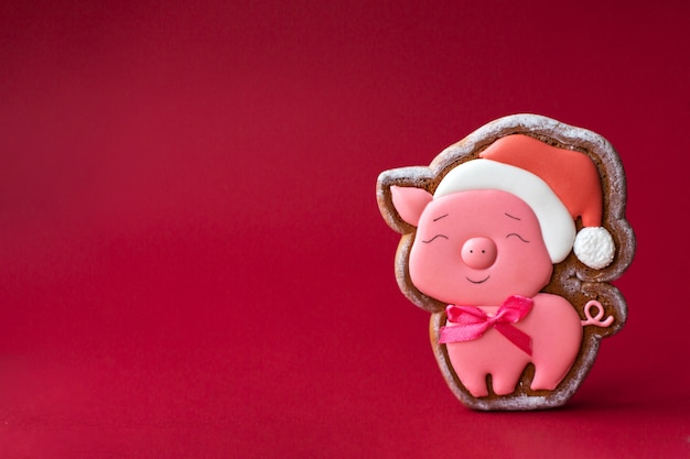 Gingerbread cookie of cute pink pig on red