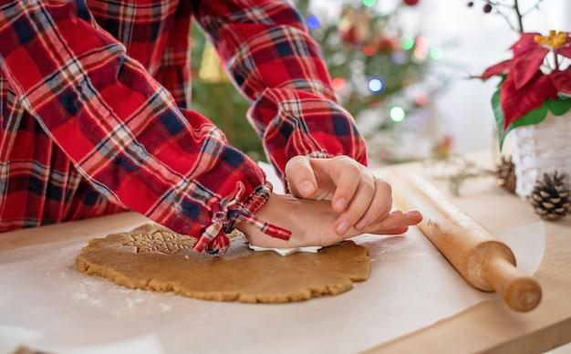 진저 브레드 쿠키 반죽. 소녀의 손은 곰팡이로 눈송이를 자릅니다. 크리스마스 굽기.