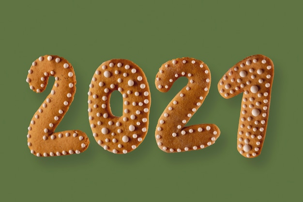 Gingerbread cookie in the form of the numbers  on a green neutral background new year concept
