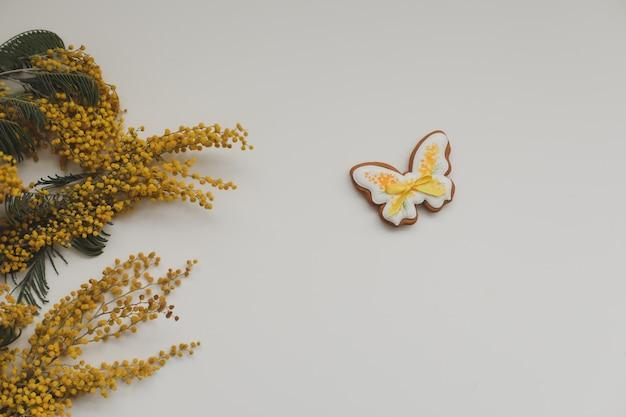 Имбирное печенье в форме бабочки и цветов мимозы на белом фоне. весна, концепция счастливой пасхи. пространство для копирования с видом сверху Premium Фотографии
