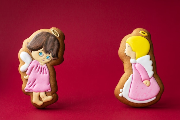 Gingerbread cookie of little cute angels on red background.