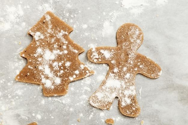 오븐에서 굽기 위해 준비된 반죽에서 진저 브레드 쿠키 새해 인물