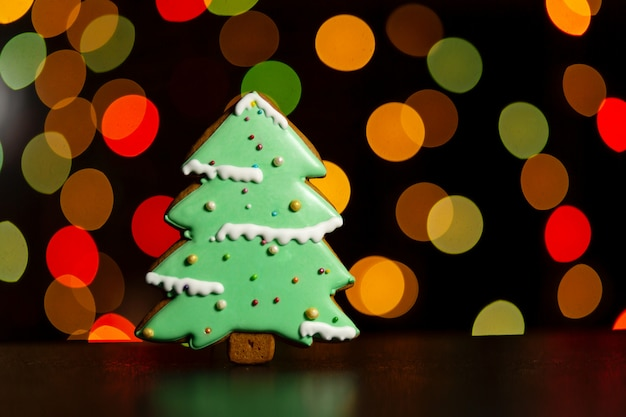 Пышное печенье зеленой рождественской елки по расфокусированным цветным огням гирлянды. традиционная рождественская еда. рождество и новый год праздник концепции.