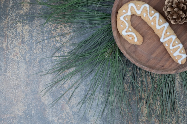 Gingerbread cookie and pinecone on wooden plate. high quality photo