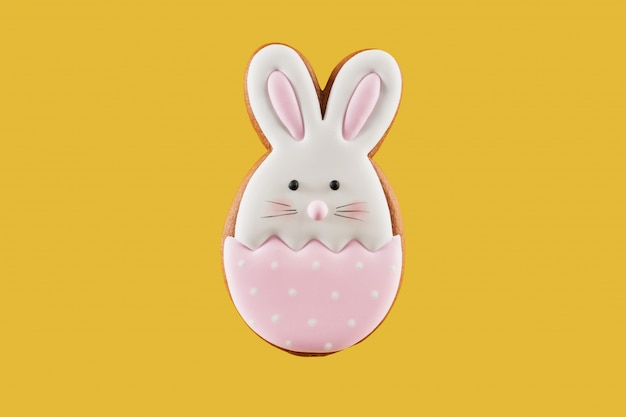 Gingerbread cookie in shape of bunny on yellow background