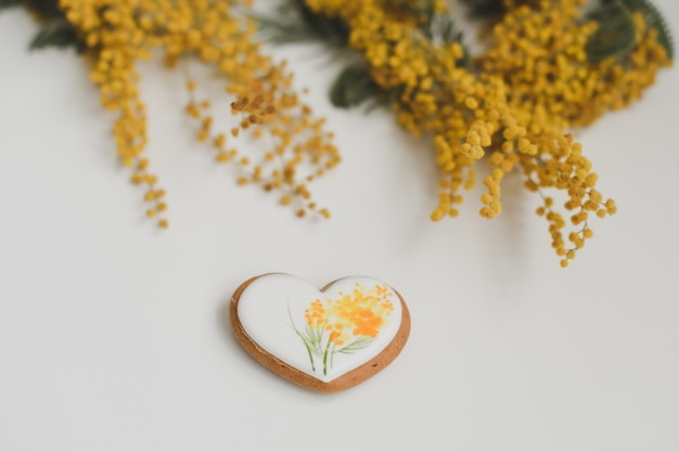 Gingerbread cookie in a shape of a heart and mimosa flowers on white background. top view copy space
