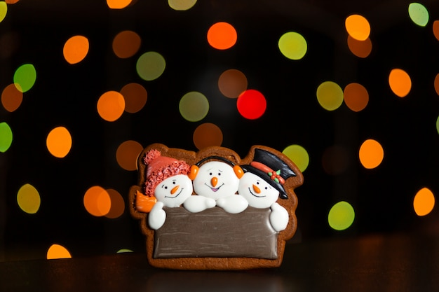 Gingerbread cookie of three snowman's portrait over blurred colored lights of garland