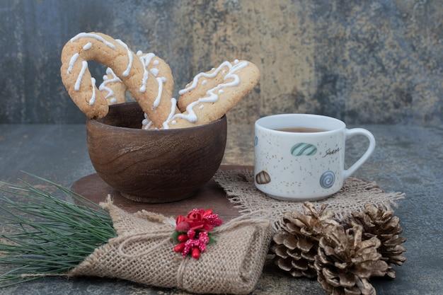 大理石のテーブルにジンジャーブレッドクッキーと松ぼっくりのお茶。高品質の写真