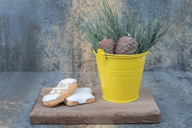 木の板にジンジャーブレッドクッキーと松ぼっくり。高品質の写真