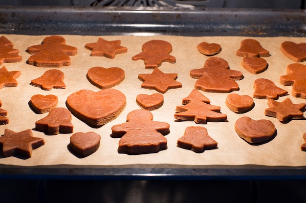 Gingerbread cookies being prepared on the baking tray in the oven