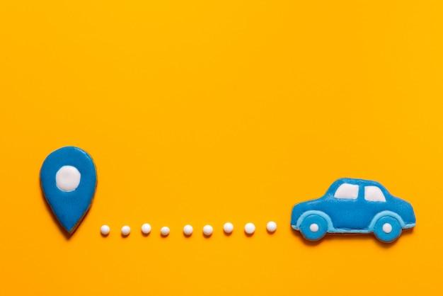 Автомобиль пряников и точка карты на желтом фоне
