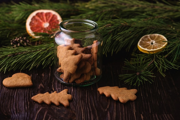 Gingerbread cookies christmas fir-tree and heart shape in glass jar on wooden table, citrus dried fruits, fir tree branch, angle view, selective focus
