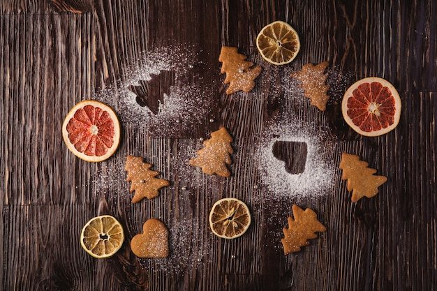 Gingerbread cookies in christmas fir-tree and heart shape, powdered sugar on wooden table, citrus dried fruits, top view