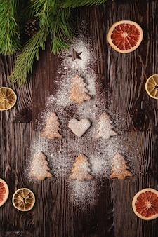 Gingerbread cookies in christmas fir-tree shape and with powdered sugar on wooden table, citrus dried fruits, fir tree branch, top view