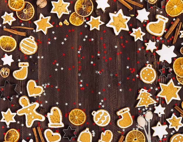 Gingerbread cookies christmas new year oranges cinnamon on wooden table with copyspace