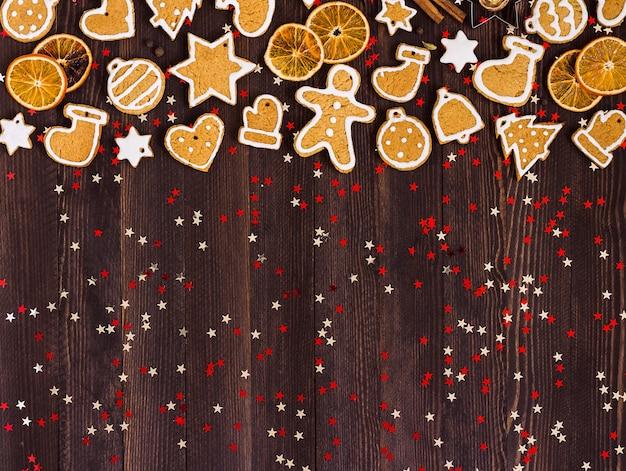 Gingerbread cookies christmas new year oranges cinnamon on wooden table