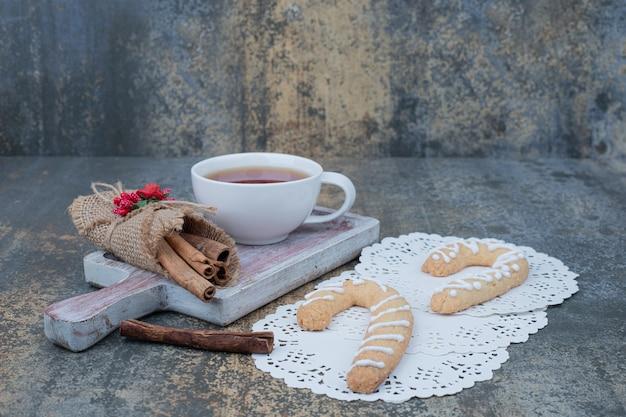 大理石のテーブルにジンジャーブレッドクッキー、シナモン、お茶を。高品質の写真