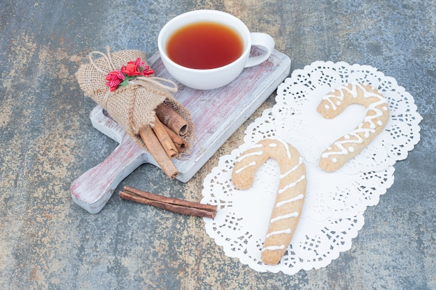 Пряники, корица и чашка чая на мраморном столе. фото высокого качества