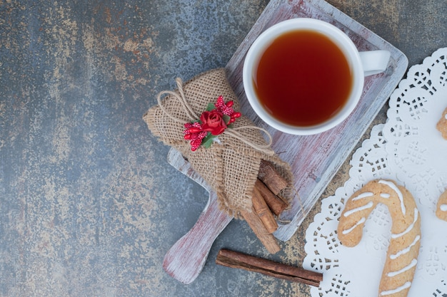 Gingerbread cookies, cinnamon and cup of tea on marble table. high quality photo