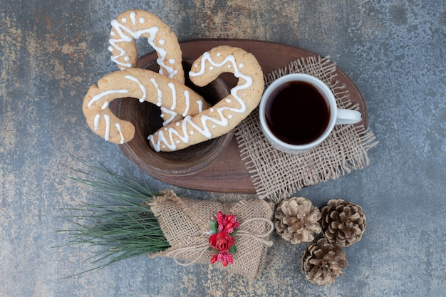 Gingerbread cookies and cup of tea with pinecones on marble table. high quality photo