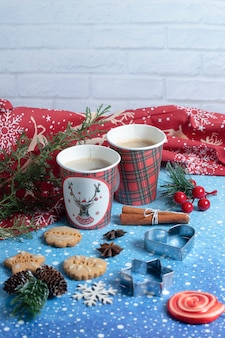 Gingerbread cookies, cups of aroma coffee and lollipop on blue