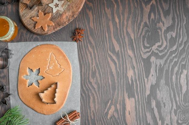 Пряники нарезка из пикантного сладкого теста на темном деревянном столе с корицей