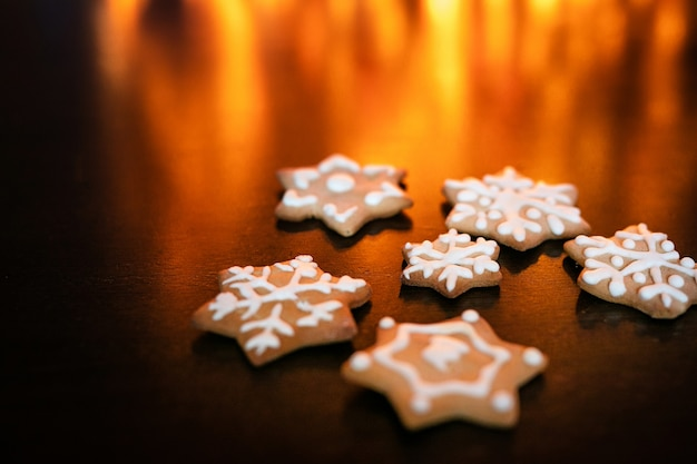 Gingerbread cookies on the dark brown table and background with golden bokeh