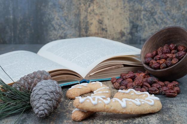 Пряники, сушеные плоды шиповника и открытая книга на мраморном фоне. фото высокого качества