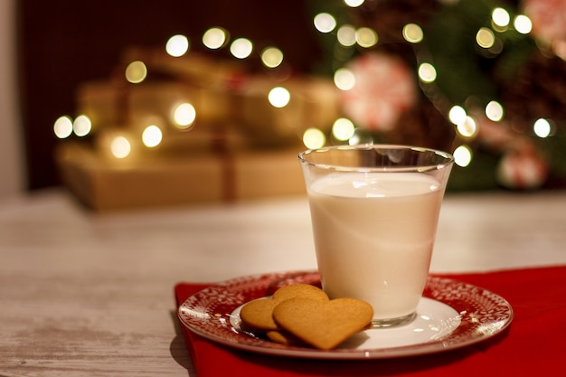 Gingerbread cookies and a glass of milk for santa claus on the background of a christmas garland and a wreath of pine needles