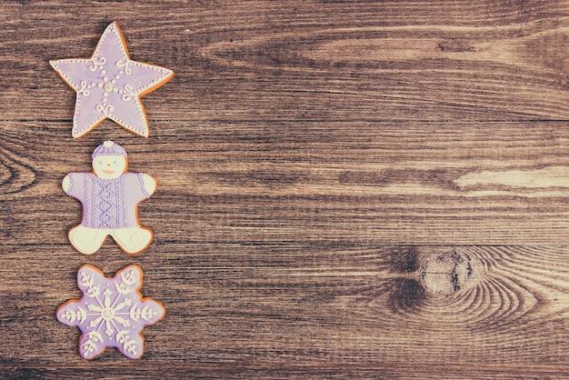 木製の背景にぶら下がっているジンジャーブレッドクッキー。スペースをコピーします。