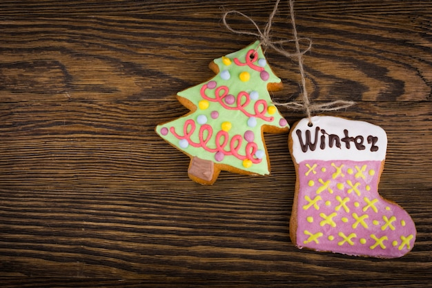 Gingerbread cookies hanging over wooden . christmas decorations top view with copy space. prepare for xmas eve or other winter holidays
