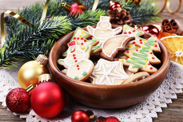 木製のテーブルの背景にクリスマスの装飾とボウルにジンジャーブレッドクッキー