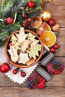 木製のテーブルにクリスマスの装飾が施されたボウルにジンジャーブレッドクッキー