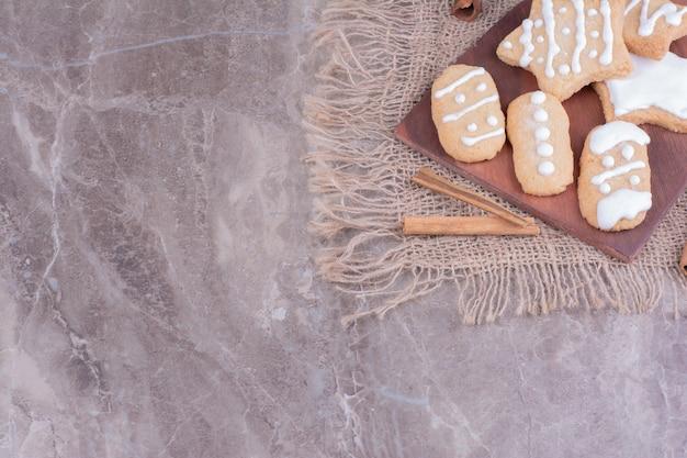 木製の大皿にシナモンスティックが付いた星型と卵形のジンジャーブレッドクッキー。